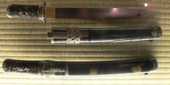Two classical Tanto, with wrapped hilts: the top knife has a straight spine and a small guard; the bottom knife has no guard, and probably a slightly curved spine